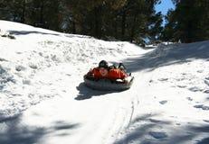 Un hombre joven compite con abajo de una colina Nevado en invierno Fotos de archivo libres de regalías