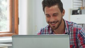 Un hombre joven comunica vía la comunicación video sobre un ordenador almacen de video