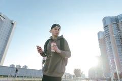 Un hombre joven con auriculares y un vidrio de la bebida caliente en sus manos, soportes en el fondo de una ciudad ajardina y esc Imagen de archivo libre de regalías