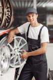 Un hombre joven con un borde del neumático en sus manos se está colocando cerca de estantes foto de archivo
