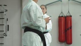 Un hombre joven con un cuerpo muscular y una mujer que practica los artes marciales Goju-Ryu Karate-hacen almacen de video
