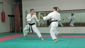 Un hombre joven con un cuerpo muscular y una mujer que practica los artes marciales Goju-Ryu Karate-hacen cámara lenta estupenda metrajes