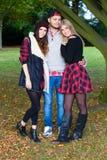 Un hombre joven con dos muchachas en un parque Fotos de archivo