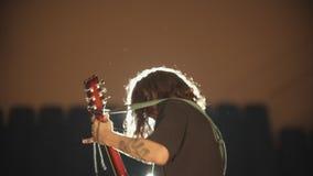Un hombre joven con el pelo largo que juega una canción en su funcionamiento y que sacude su cabeza almacen de video
