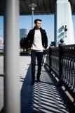 Un hombre joven con el pelo oscuro y los ojos que camina abajo de la calle lifestyle Elevado crecimiento Imagen de archivo