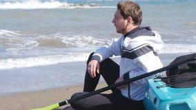 Un hombre joven con un kajak en la costa almacen de metraje de vídeo