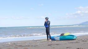 Un hombre joven con un kajak en la costa almacen de video