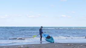 Un hombre joven con un kajak en la costa metrajes