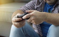 Un hombre joven con la palanca de mando que juega a los videojuegos en casa que pasa t Foto de archivo libre de regalías