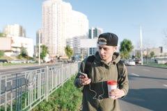 Un hombre joven con los auriculares en los oídos y el café en el yugo da un paseo alrededor de la ciudad y utiliza el teléfono Imagen de archivo