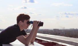 Un hombre joven con los prismáticos que mira del tejado de la casa Fotos de archivo