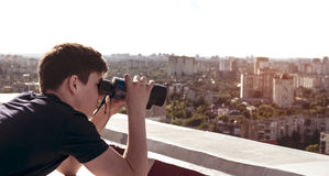 Un hombre joven con los prismáticos que mira del tejado de la casa Imagen de archivo libre de regalías