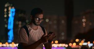 Un hombre joven con los vidrios en las miradas de la noche en la pantalla de un smartphone almacen de metraje de vídeo
