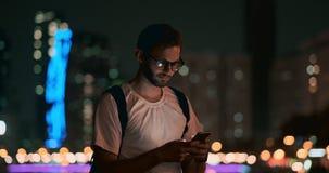 Un hombre joven con los vidrios en las miradas de la noche en la pantalla de un smartphone almacen de video