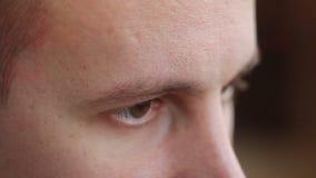 Un hombre joven con marrón observa la mirada al lado, un efecto del ordenador metrajes