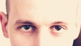 Un hombre joven con marrón observa la mirada en la cámara almacen de video