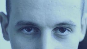 Un hombre joven con marrón observa la mirada en la cámara almacen de metraje de vídeo