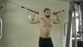Un hombre joven con un torso desnudo se divierte una constitución en el gimnasio, haciendo ejercita para los músculos de las mano almacen de video
