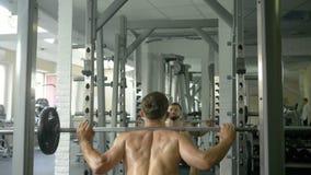 Un hombre joven con un torso desnudo se divierte una constitución en el gimnasio, haciendo ejercita para los músculos traseros, u almacen de metraje de vídeo