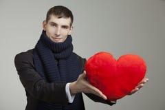 Un hombre joven con un corazón rojo Foto de archivo libre de regalías