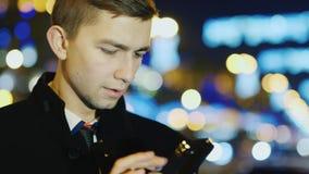 Un hombre joven con un teléfono móvil en la ciudad de la noche metrajes