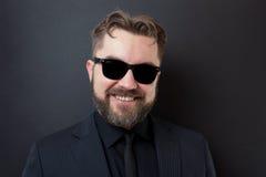 Un hombre joven con una barba en un traje de negocios negro elegante se coloca en un fondo negro y sonríe Fotografía de archivo libre de regalías