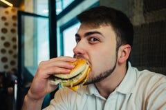 Un hombre joven con una barba goza de los alimentos de preparación rápida Foto de archivo
