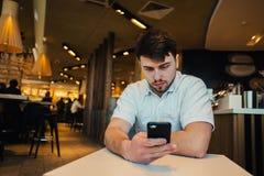 Un hombre joven con una barba goza del teléfono en restaurante acogedor Fotos de archivo