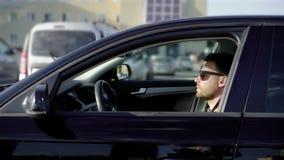 Un hombre joven con una barba monta en el estacionamiento en su coche negro El sedán del negocio se mueve reservado a lo largo de almacen de metraje de vídeo