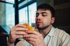Un hombre joven con una barba que mira que va a una hamburguesa y la come Imagen de archivo libre de regalías