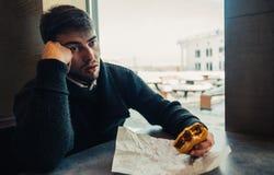 Un hombre joven con una barba, sentándose en un restaurante y puede comer no más encima de su hamburguesa Imagenes de archivo