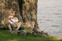 Un hombre joven con una bici en naturaleza Fotos de archivo
