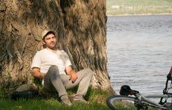 Un hombre joven con una bici en naturaleza Foto de archivo libre de regalías