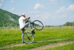 Un hombre joven con una bicicleta Imagen de archivo libre de regalías