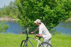 Un hombre joven con una bicicleta en fondo de la naturaleza Fotos de archivo libres de regalías