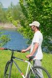 Un hombre joven con una bicicleta en fondo de la naturaleza Foto de archivo