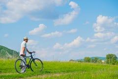 Un hombre joven con una bicicleta en fondo de la naturaleza Fotos de archivo