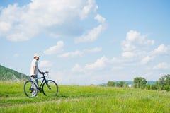 Un hombre joven con una bicicleta en fondo de la naturaleza Fotografía de archivo libre de regalías