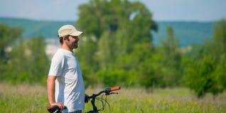 Un hombre joven con una bicicleta en fondo de la naturaleza Foto de archivo libre de regalías
