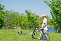 Un hombre joven con una bicicleta en fondo de la naturaleza Imagen de archivo