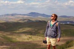 Un hombre joven con una cámara en las montañas Imágenes de archivo libres de regalías