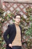Un hombre joven con una cara pensativa presenta cerca de la pared con un enrejado de madera adornado con la hiedra artificial Ves fotografía de archivo
