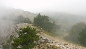 Un hombre joven con una mochila en sus hombros camina a lo largo de un canto de la montaña rocosa cubierto con las nubes almacen de video