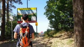 Un hombre joven con una mochila que estudia al tablero de la información en naturaleza Alza en la bosque-playa almacen de video