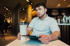 Un hombre joven con una tableta y una bebida de restauración en el restaurante acogedor se sienta Fotos de archivo libres de regalías