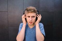 Un hombre joven concesionario escucha la música en los auriculares en la parte de atrás de una pared gris Imagen de archivo