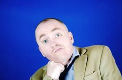 Un hombre joven confuso o sorprendido con los ojos azules puso su puño debajo de su barbilla Expresi?n facial de la emoci?n imagen de archivo