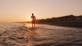 Un hombre joven corre alrededor de la resaca en la puesta del sol Hacer deportes en el centro turístico metrajes