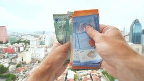 Un hombre joven cuenta de nuevo en sus manos el dinero de Malasia contra la perspectiva del centro de ciudad de Kuala Lumpur almacen de video