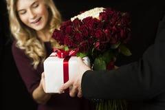 Un hombre joven da a regalo una caja blanca con un arco rojo y las flores a una muchacha en un fondo negro aislado Concepto del d fotos de archivo
